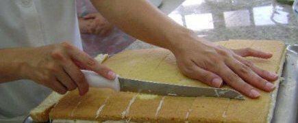 cortando bolo de coco recheado